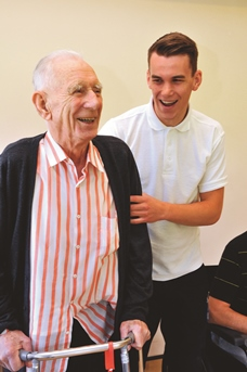 Therapist supports an elderly gentleman in recovery from stroke