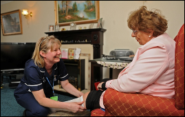 A community nurse tends to a patients leg wound in their own home